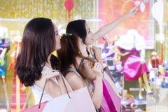 Tres chicas jóvenes que hacen compras junto Foto de archivo
