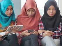 Tres chicas jóvenes que llevan el hijab usando los dispositivos móviles fotografía de archivo libre de regalías