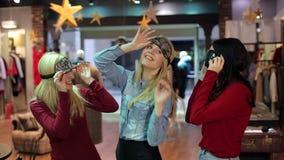 Tres chicas jóvenes que llevan máscaras el dormir y divertirse en la tienda de ropa almacen de video