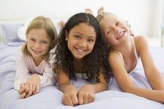 Tres chicas jóvenes que mienten en una cama en sus pijamas Imagen de archivo
