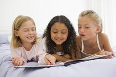Tres chicas jóvenes que mienten en una cama en sus pijamas Foto de archivo libre de regalías