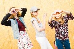 Tres chicas jóvenes que presentan en las calles de la ciudad - forma del corazón - diversión adentro foto de archivo libre de regalías