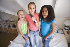 Tres chicas jóvenes que se colocan en una cama Fotos de archivo libres de regalías