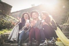 Tres chicas jóvenes que se sientan en las escaleras en el parque público foto de archivo