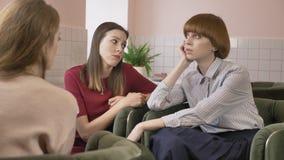 Tres chicas jóvenes se están sentando en los cafés, agujereados, los amigos, compañía, chismes, diálogo, discusión Novias en el c almacen de metraje de vídeo