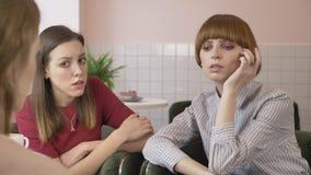 Tres chicas jóvenes se están sentando en los cafés, agujereados, los amigos, compañía, chismes, diálogo, discusión Novias en el c metrajes