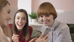 Tres chicas jóvenes se están sentando en un café, riendo, sonriendo, amigos, compañía, chismes, diálogo, discusión novias metrajes