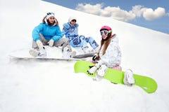 Tres chicas jóvenes se sientan en nieve Fotografía de archivo libre de regalías