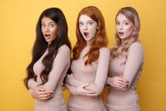 Tres chocaron a señoras con los brazos cruzados que presentaban en estudio Fotos de archivo