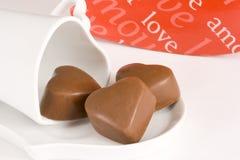 Tres chocolates en forma de corazón en una taza y un platillo fotos de archivo