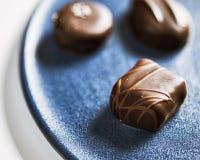 Tres chocolates en una placa de cerámica azul imagen de archivo