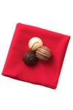 Tres chocolates en una servilleta roja Fotos de archivo libres de regalías