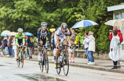 Tres ciclistas que montan en la lluvia Imagen de archivo libre de regalías