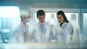 Tres científicos que trabajan en un laboratorio de investigación metrajes