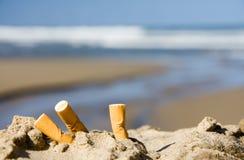 Tres cigarrillos en la playa Fotografía de archivo libre de regalías