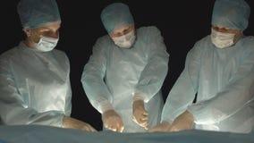 Tres cirujanos, hombre y mujer, realizan cirugía en la sala de operaciones de quitar y trasplantar los órganos humanos, reseque almacen de metraje de vídeo
