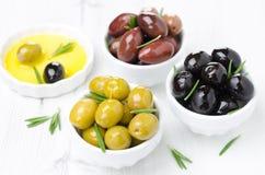 Tres clases de aceitunas en cuencos, romero fresco y aceite de oliva Fotografía de archivo