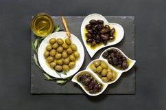 Tres clases de aceitunas y de aceite de oliva seleccionados Imágenes de archivo libres de regalías