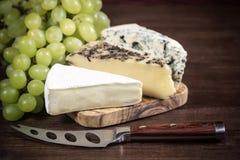 Tres clases de queso y de uvas del vino blanco Foto de archivo