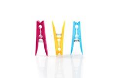 Tres clavijas de ropa plásticas coloreadas de lado a lado Fotografía de archivo