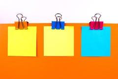 Tres clips de la carpeta en el papel con el fondo Imagen de archivo libre de regalías