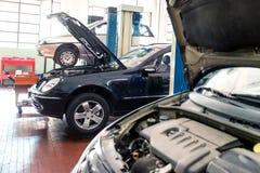 Tres coches en un taller de reparaciones Fotografía de archivo libre de regalías
