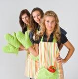 Tres cocineros de sexo femenino que saludan Imagenes de archivo