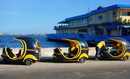 Tres Cocotaxis y sus conductores en el puerto de La Habana Fotografía de archivo