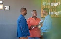 Tres colegas africanos sonrientes que hablan negocio junto en una oficina Imagen de archivo libre de regalías