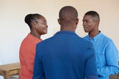 Tres colegas de oficina africanos sonrientes que hablan junto en el trabajo Imagen de archivo