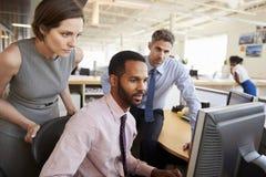 Tres colegas del negocio que trabajan junto alrededor de un monitor imagen de archivo libre de regalías