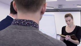 Tres colegas están discutiendo el gráfico de la tarifa del bitcoin en la sala de reunión almacen de video