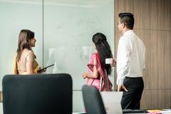 Tres colegas indios que escriben ideas durante la reunión de reflexión foto de archivo