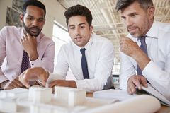 Tres colegas masculinos que discuten un modelo arquitectónico foto de archivo