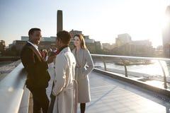 Tres colegas milenarios se colocan que hablan en el puente del milenio mientras que va el sol abajo fotografía de archivo
