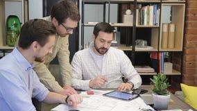 Tres colegas que hablan con la tableta que se sienta en oficina moderna dentro metrajes