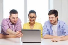 Tres colegas sonrientes con el ordenador portátil en oficina Foto de archivo libre de regalías