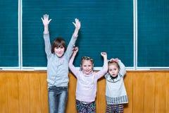 Tres colegialas felices en la pizarra Imagenes de archivo
