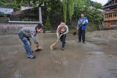Tres colegiales rurales chinos barren la risa del terreno de la escuela Fotografía de archivo libre de regalías
