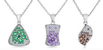 Tres colgantes de plata de diversas formas en una cadena Imagen de archivo libre de regalías