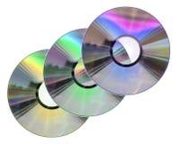 Tres colorearon discos del CD/DVD aislados en blanco Imagen de archivo libre de regalías