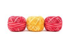 Tres colorearon hilos de coser en fila en un fondo blanco Hilos del rojo y del amarillo Imagenes de archivo