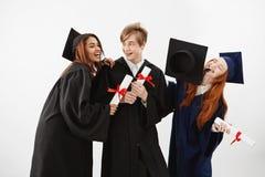 Tres compañeros de clase graduados alegres que celebran disfrutar sonriente sobre el fondo blanco Abogados o médicos futuros Foto de archivo libre de regalías