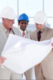 Tres compañeros de trabajo del ingeniero que estudian planes imagen de archivo
