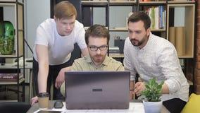 Tres compañeros de trabajo discuten la información usando el ordenador en oficina metrajes