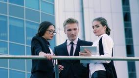 Tres compañeros de trabajo que se colocan en la terraza del edificio de oficinas y que hablan de su día laborable y reuniones almacen de metraje de vídeo