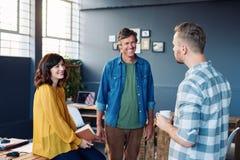 Tres compañeros de trabajo que sonríen y que hablan junto en una oficina moderna Imágenes de archivo libres de regalías