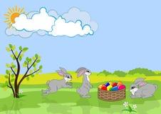 Tres conejos y cestas de Pascua con los huevos del color. Fotos de archivo libres de regalías