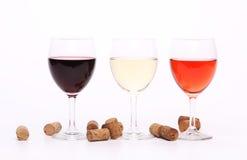 Tres copas de vino y corchos. Imagenes de archivo