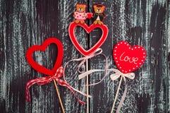 Tres corazones de madera rojos en un colorido superficial negro Fotos de archivo libres de regalías